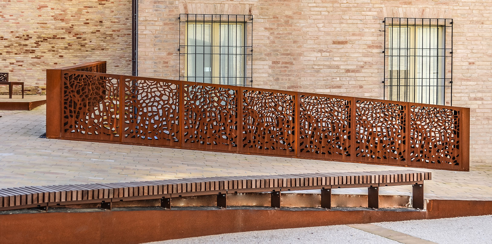 ramp delimited by a laser engraved steel railing and corten borders